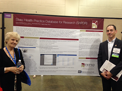 NIH and contractor staff standing in front of SHPDR poster