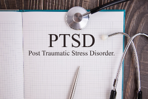 Notebook page with text PTSD on a table with a stethoscope and pen