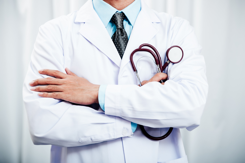 Doctor folding arms holding stethoscope