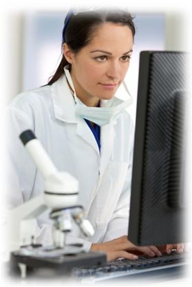Lab worker looking at a computer with a microscope in the foreground