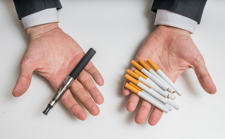 Hands holding e-cigarettes and tobacco cigarettes