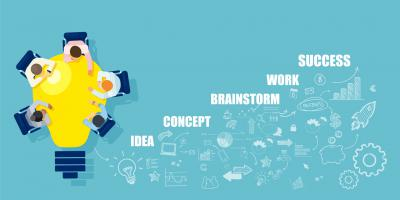 Cartoon of people sitting around a lightbulb shaped table with the words: idea, concept, brainstorm, work, success