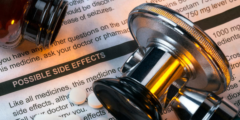 Image of medication and a stethoscope on top of papers listing side effects