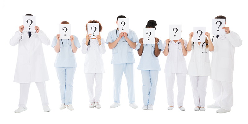 Doctors holding signs with question marks