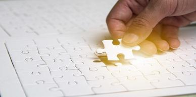 Hand inserting missing jigsaw to make complete picture