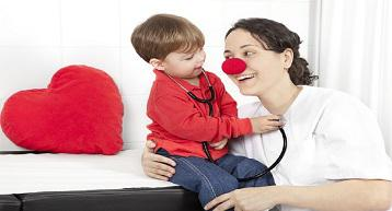 Doctor with clown nose smiling while child uses stethoscope on her