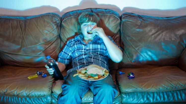 Child eating unhealthy snacks while watching TV