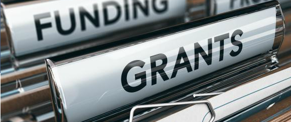 "An image of a filing cabinet that says ""funding"" and ""grants"""