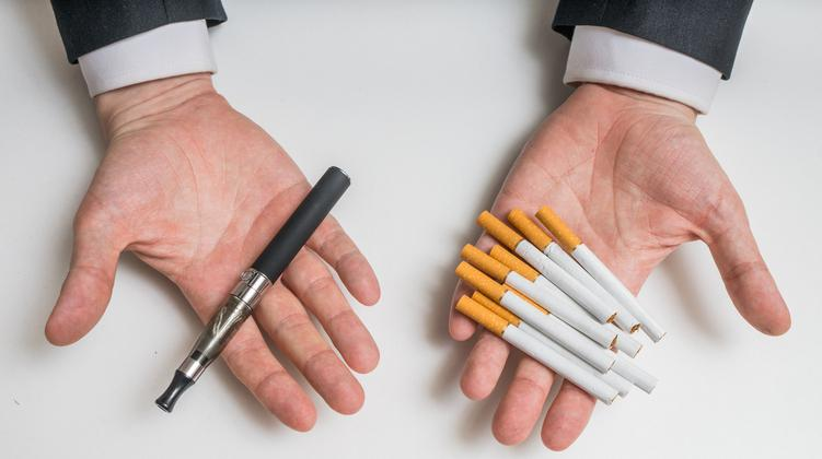 hands holding electronic and conventional cigarette