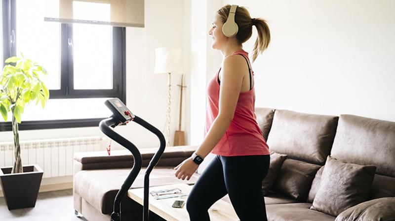Woman exercising on treadmill in her living room